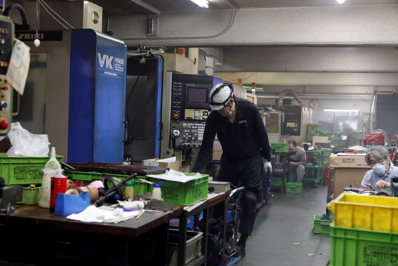 Workers are seen at flood-damaged metal processing factory in Kawasaki