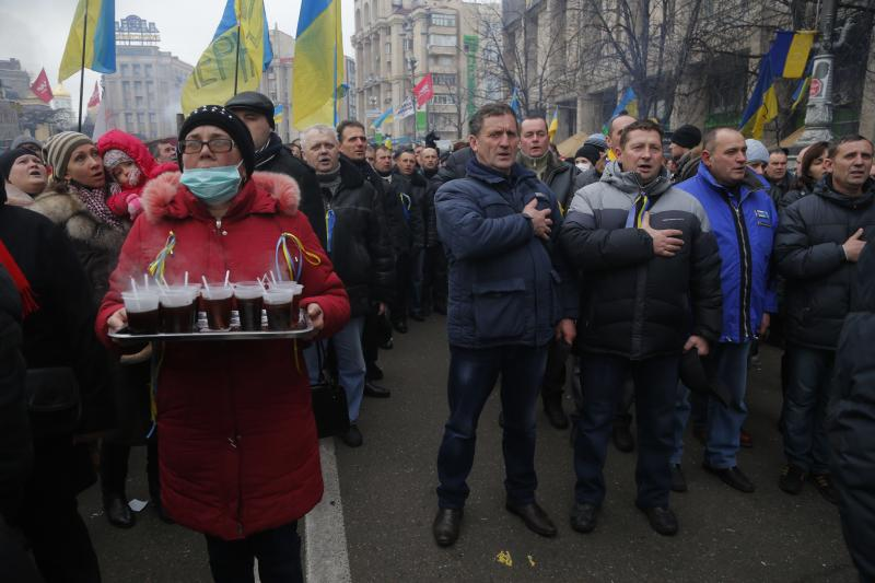 A volunteer carrying a tray with tea stands as other Ukrainians sing the national anthem during a Pro-European Union rally in Independence Square in Kiev, Ukraine, Sunday, Dec. 15, 2013. About 200,000 anti-government demonstrators converged on the central square of Ukraine's capital Sunday, a dramatic demonstration that the opposition's morale remains strong after nearly four weeks of daily protests. (AP Photo/Sergei Grits)
