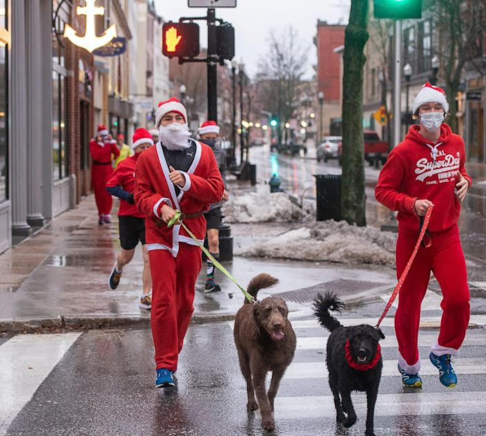 Maxi Kolb, an exchange student from Germany, and Lukas Hradecky, an exchange student from the Czech Republic, participate in a  Santa run on wet streets Christmas morning run in Lewiston, Maine.