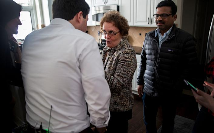 Carol Hunter, executive editor of the Des Moines Register asks Pete Buttigieg, mayor of South Bend, Ind., a question as he makes his way through the crowd on Saturday, Feb. 9, 2018, in the living room of a home in Johnston. Buttigieg is exploring a run for president.