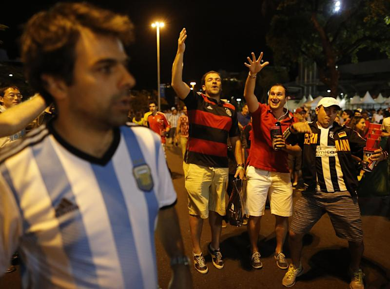 Brazil soccer fans wearing colors of the German national team, joke around with an Argentina soccer fan, left, outside the Maracana stadium after the World Cup final match between Argentina and Germany in Rio de Janeiro, Brazil, Sunday, July 13, 2014. Mario Goetze volleyed in the winning goal in extra time to give Germany its fourth World Cup title with a 1-0 victory over Argentina