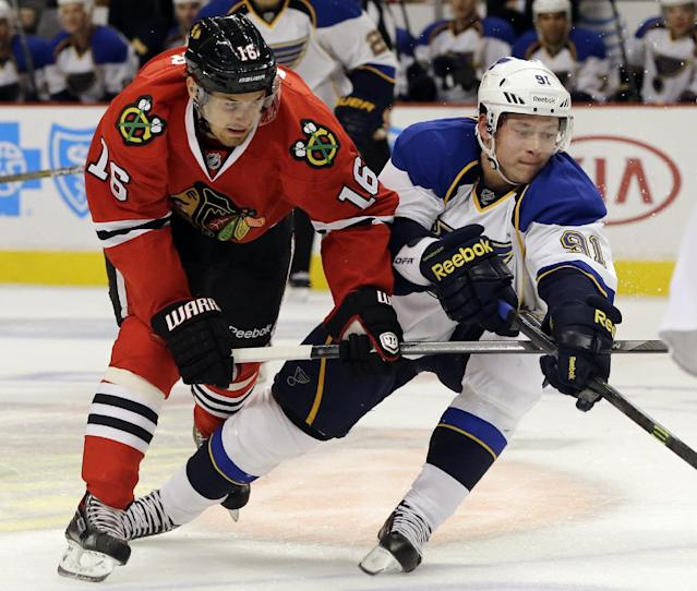 St. Louis Blues' Vladimir Tarasenko (91) chases the puck as he battles against Chicago Blackhawks' Marcus Kruger (16) during the first period of an NHL hockey game in Chicago, Thursday, Oct. 17, 2013. (AP Photo/Nam Y. Huh)