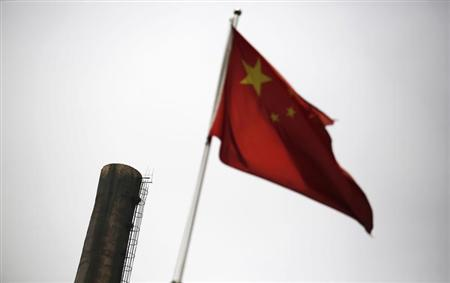 A Chinese national flag is seen in front of a chimney of a heat supply plant in Beijing