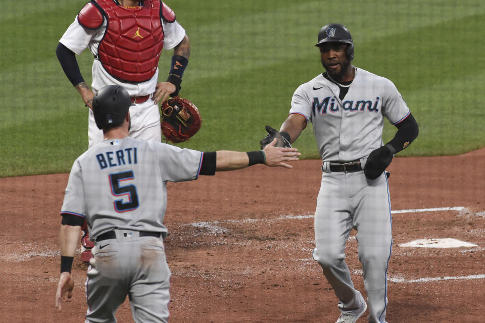 Miami Marlins center fielder Starling Marte, right, and teammate Miami Marlins' Jon Berti react after scoring two runs against the St. Louis Cardinals during the third inning of a baseball game Monday, June 14, 2021, in St. Louis. (AP Photo/Joe Puetz)