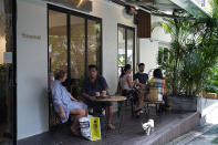 Customers sit in at tables outside the Found Cafe in Hong Kong on Sept. 13, 2020. Cannabis, also known as marijuana, in Hong Kong may be illegal, but the new Found Cafe is offering a range of food and drinks that contain parts of the cannabis plant without breaking any local laws. (AP Photo/Vincent Yu)