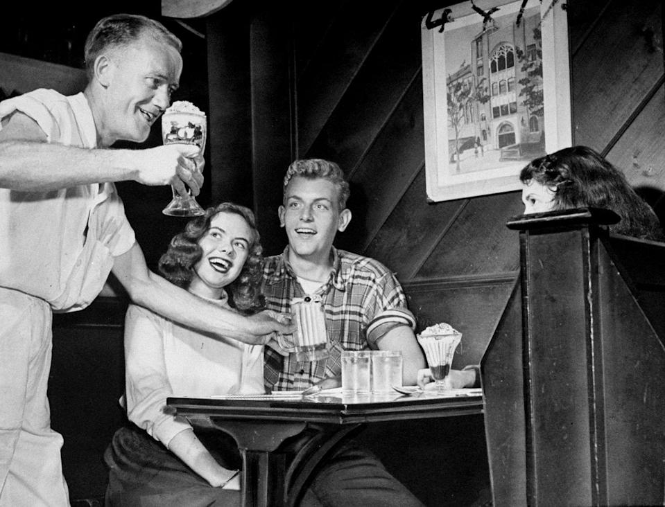 """<p>A soda jerk serves a milkshake to a table of eager customers. <a href=""""https://www.history.com/news/ice-cream-boom-1920s-prohibition"""" rel=""""nofollow noopener"""" target=""""_blank"""" data-ylk=""""slk:&quot;Soda jerks&quot;"""" class=""""link rapid-noclick-resp"""">""""Soda jerks""""</a> were a common title for the employee who served ice cream and soda behind the parlor counter.</p>"""