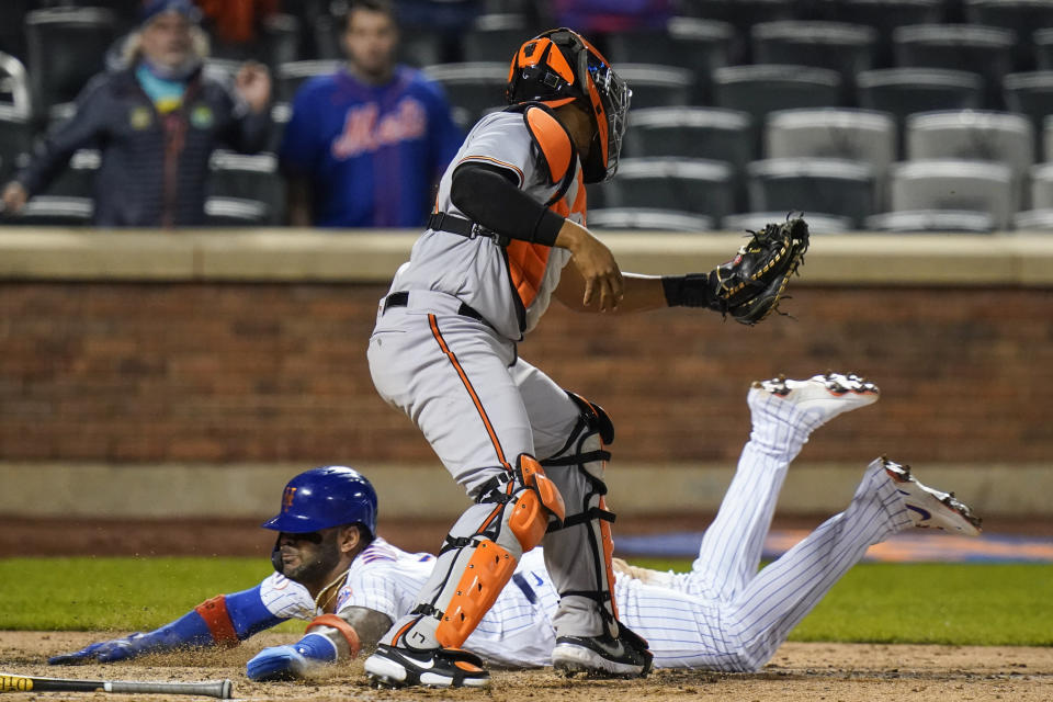 New York Mets' Jonathan Villar slides past Baltimore Orioles catcher Pedro Severino to score the game-winning run during in a baseball game Tuesday, May 11, 2021, in New York. The Mets won 3-2. (AP Photo/Frank Franklin II)