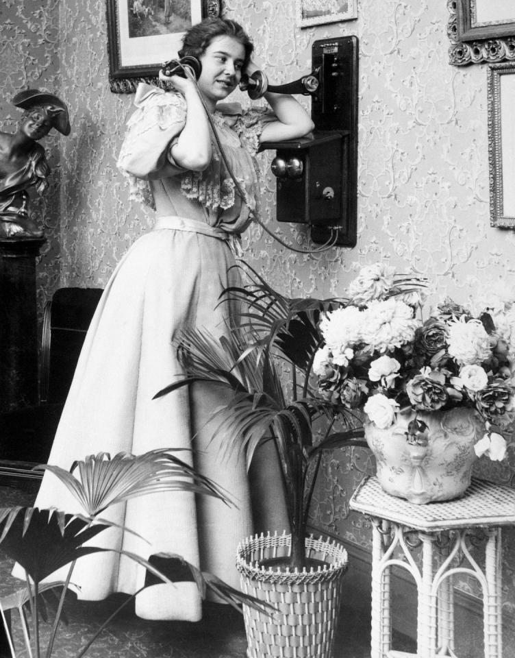 <p>A Victorian woman uses the parlor telephone.</p>