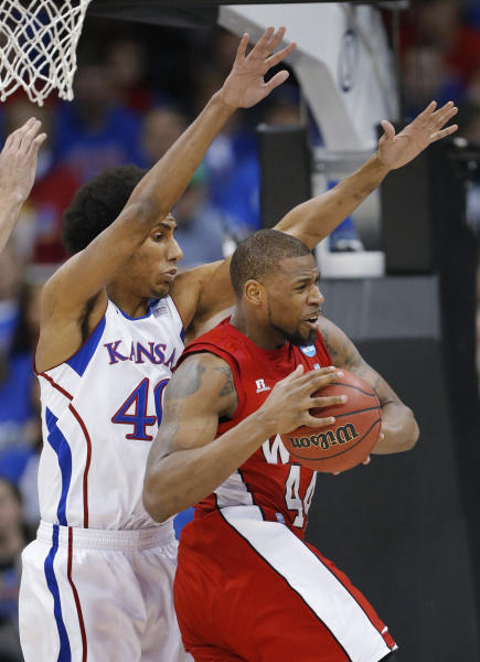 Western Kentucky forward George Fant (44) is covered by Kansas forward Kevin Young (40) during the first half of a second-round game in the NCAA men's college basketball tournament in Kansas City, Mo., Friday, March 22, 2013. (AP Photo/Orlin Wagner)