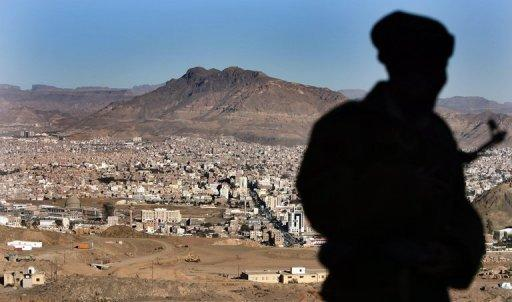 A Yemeni soldier stands on a hill overlooking Saana