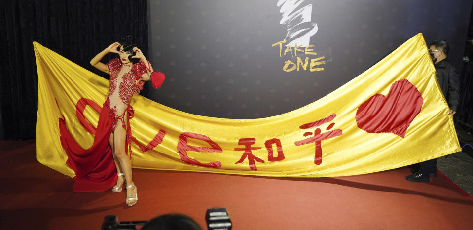 "Chinese-American actress Bai Ling poses with her slogan ""Love, Peace"" at the 57th Golden Horse Awards in Taipei, Taiwan, Saturday, Nov. 21, 2020. Bai is nominated for Best Leading Actress for the film ""The Abortionist"" at this year's Golden Horse Awards -one of the Chinese-language film industry's biggest annual events. (AP Photo/Billy Dai)"