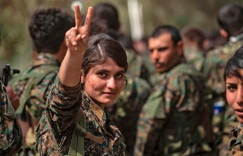 A female fighter of the US-backed Kurdish-led Syrian Democratic Forces (SDF) flashes the victory gesture while celebrating near the Omar oil field in the eastern Syrian Deir Ezzor province on March 23, 2019, after announcing the total elimination of the Islamic State (IS) group's last bastion in eastern Syria. - Credit: AFP