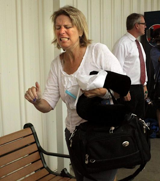 A passenger on a bus that crashed just north of Litchfield grimaces as she walks to a shelter set up for travelers not seriously injured in Litchfield, Ill. on Thursday, August 2, 2012. (AP Photo/St. Louis Post-Dispatch, Christian Gooden) EDWARDSVILLE INTELLIGENCER OUT; THE ALTON TELEGRAPH OUT