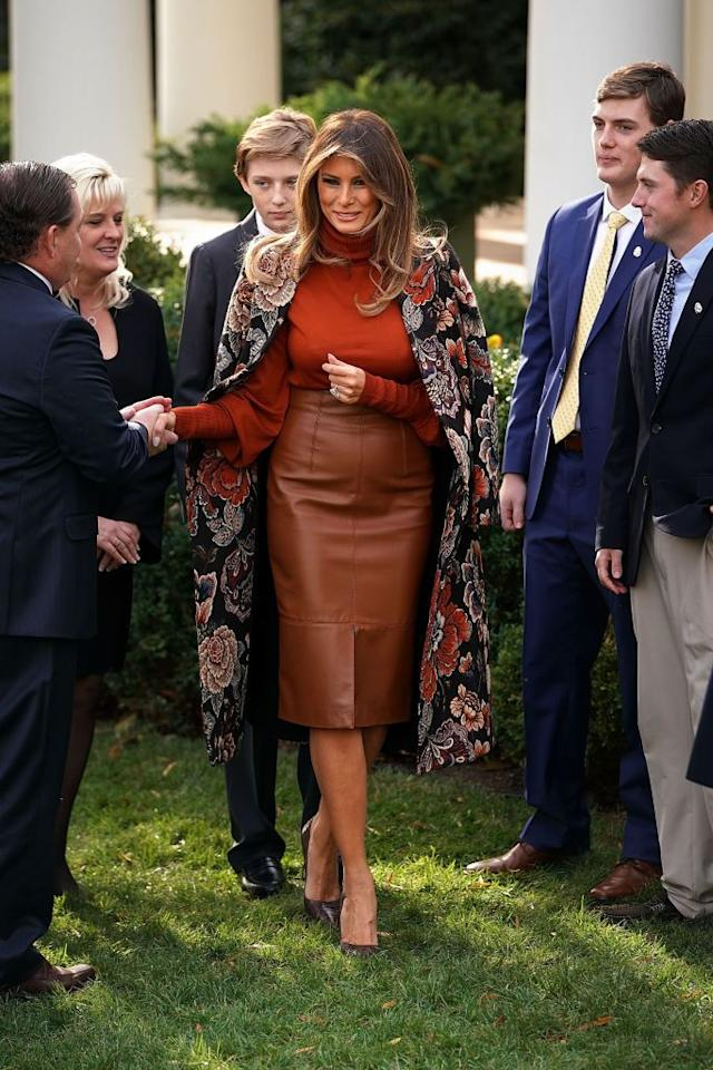 "<p>The First Lady went seasonal with a burnt orange blouse, Stella McCartney floral coat, and brown leather skirt for <a href=""https://www.townandcountrymag.com/society/a13814273/presidential-turkey-pardon/"" target=""_blank"">the annual White House turkey pardon</a>.</p>"
