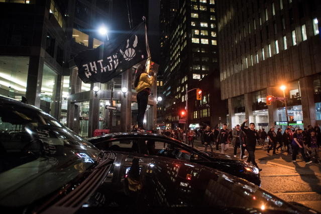 A fan waves a Toronto Raptors support flag on top of a car as fans celebrate early Friday, June 14, 2019, on the streets of Toronto following the Raptors' 114-110 win over the Golden State Warriors in Oakland, Calif., in Game 6 of basketball's NBA Finals. (Tijana Martin/The Canadian Press via AP)