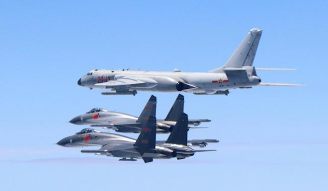 A PLA H-6K bomber flies in formation with two J-11 fighter jets. Photo: Xinhua