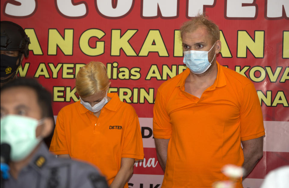 Russian citizens Andrei Kovalenka, right, and his partner Ekaterina Trubkina stand during a press conference at the immigration office in Jimbaran, Bali, Indonesia, Wednesday, Feb. 24, 2021. Kovalenka, listed by the Interpol as a fugitive back home, was arrested on the Indonesian tourist island of Bali on Wednesday after 13 days on the run with his partner to avoid deportation. (AP Photo/Firdia Lisnawati)