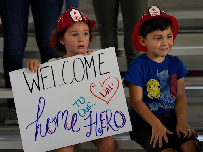 """Two children hold a sign that says """"Welcome home to our hero."""""""