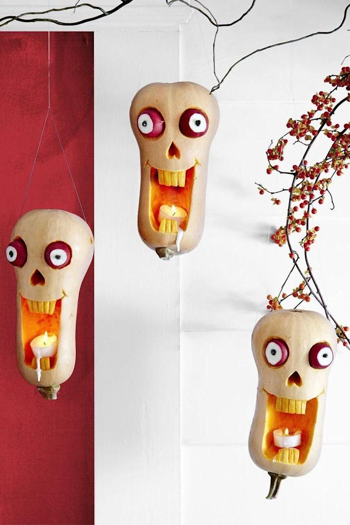 """<p>To make these funny skull pumpkins, draw tall rectangle mouth, teeth and smile lines on butternut squash with a highlighter. Carve mouth and lines, then etch skin off teeth with linoleum cutter. Hollow out inside of mouth only, and carve upside-down heart for nose. Cut eye sockets with top of knife tilted toward the pumpkin. Slice an end off 2 radishes and push in black beans for pupils, then add 2 toothpicks to back of each and push into sockets. Poke deep hole in either side of squash at top with an awl. Tape a length of monofilament to wood skewer and thread through holes; discard skewer. Knot ends of monofilament together and use loop to hang.</p><p><a class=""""link rapid-noclick-resp"""" href=""""https://www.amazon.com/Makerstep-Toothpicks-Cocktail-Appetizer-Barbecue/dp/B07WC2X2B4?tag=syn-yahoo-20&ascsubtag=%5Bartid%7C10070.g.2488%5Bsrc%7Cyahoo-us"""" rel=""""nofollow noopener"""" target=""""_blank"""" data-ylk=""""slk:SHOP TOOTHPICKS"""">SHOP TOOTHPICKS</a></p>"""