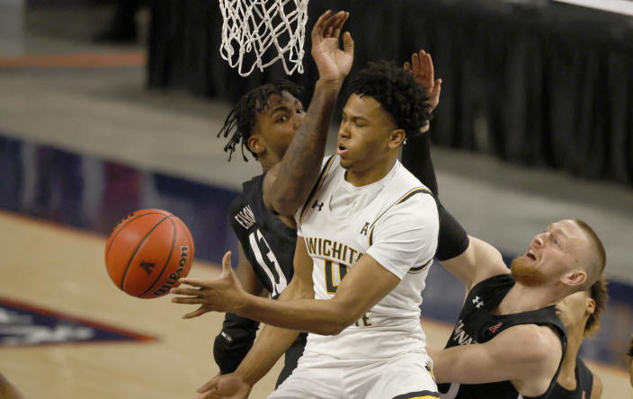 Wichita State guard Ricky Council IV, center, tries to pass around Cincinnati forward Tari Eason, left, and Cincinnati guard Mason Madsen, right, during the first half of an NCAA college basketball game in the semifinal round of the American Athletic Conference men's tournament Saturday, March 13, 2021, in Fort Worth, Texas. (AP Photo/Ron Jenkins)