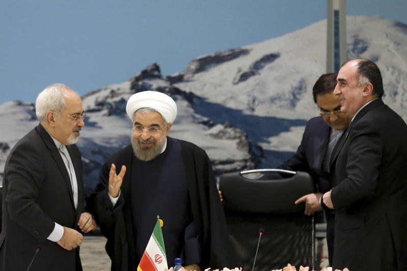 From left to right Mohammad Javad Zarif, Iran's foreign minister, Hassan Rouhani, Iran's president, and Elmar Mammadyarov, Azerbaijan's foreign minister attend the ECO council of ministers in Tehran, Iran on Tuesday, Nov. 26, 2013. Even before Iran's envoys could pack their bags in Geneva after wrapping up a first-step nuclear deal with world powers, President Rouhani was opening a potentially tougher diplomatic front: Selling the give-and-take to his country's powerful interests led by the Revolutionary Guard. Whether Iran's hard-liners will aid or obstruct expanded UN inspections and other points of the accord stands as the biggest wild card on whether it can hit it marks and test Iran's claims that it does not seek nuclear weapons. (AP Photo/Ebrahim Noroozi)