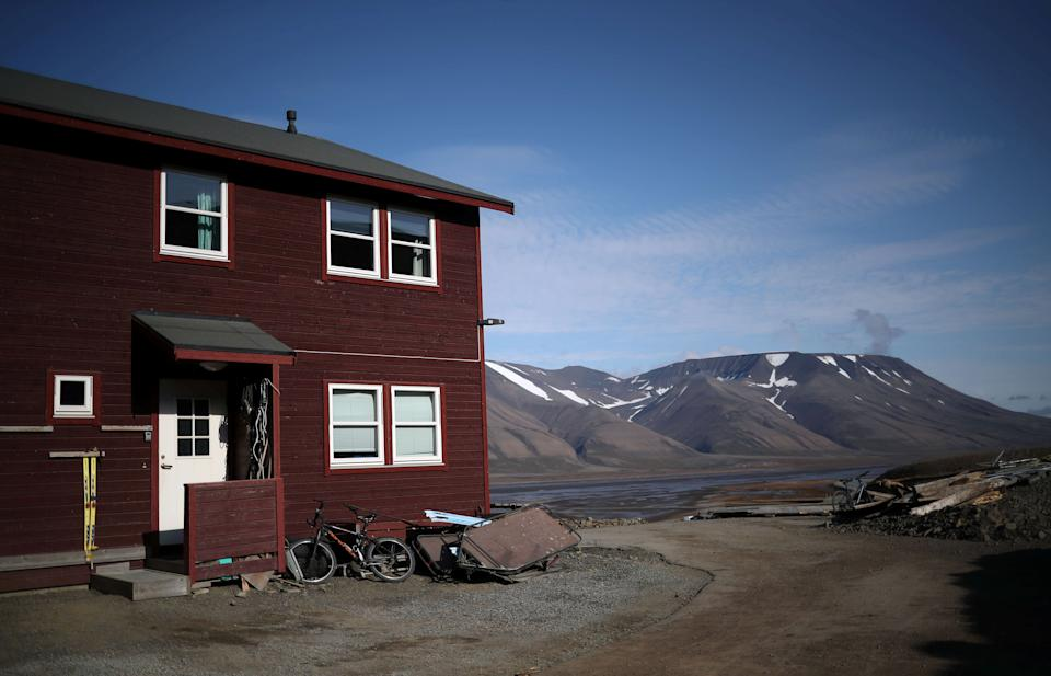 "A residential house is seen in front of snow capped mountains in the town of Longyearbyen in Svalbard, Norway, August 4, 2019. REUTERS/Hannah McKay      SEARCH ""SVALBARD CLIMATE"" FOR THIS STORY. SEARCH ""WIDER IMAGE"" FOR ALL STORIES."