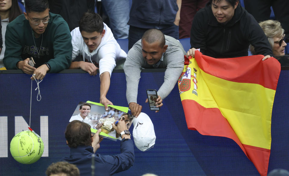 Spain's Rafael Nadal signs autographs for fans on Rod Laver Arena during the ATP Cup in Melbourne, Australia, Tuesday, Feb. 2, 2021. The Australian Open site has the feel of a major this week with six tournaments being contested at Melbourne Park. Usually the tuneup tournaments Down Under are spread around the capital cities and some of the biggest stars have time off competitive play in the week before the first Grand Slam of the season. Not this year. The COVID-19 pandemic has changed the entire preparation for the Australian Open.(AP Photo/Hamish Blair)