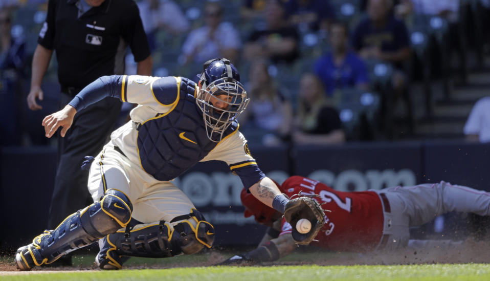 Cincinnati Reds right fielder Nick Castellanos (2) slides into home ahead of the tag by Milwaukee Brewers catcher Manny Pina (9) during the fourth inning of a baseball game Wednesday, June 16, 2021, in Milwaukee. (AP Photo/Jeffrey Phelps)