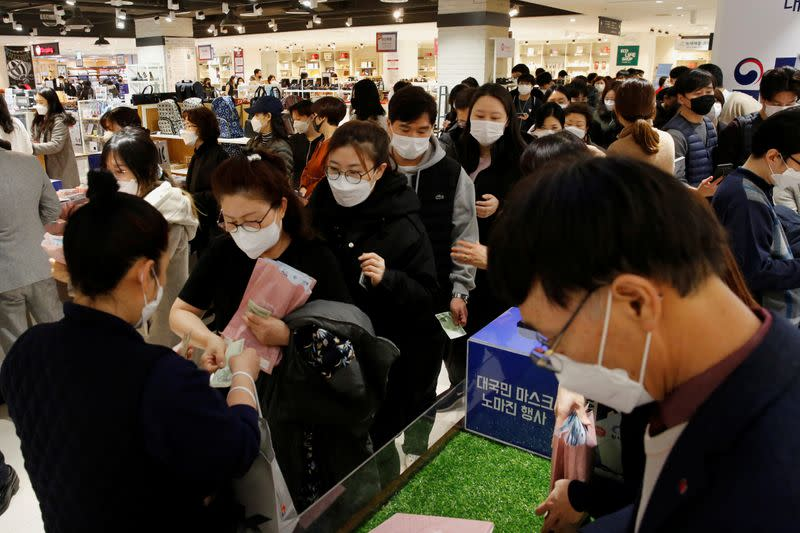 People wearing masks to prevent contracting the coronavirus wait in line to buy masks at a department store in Seoul