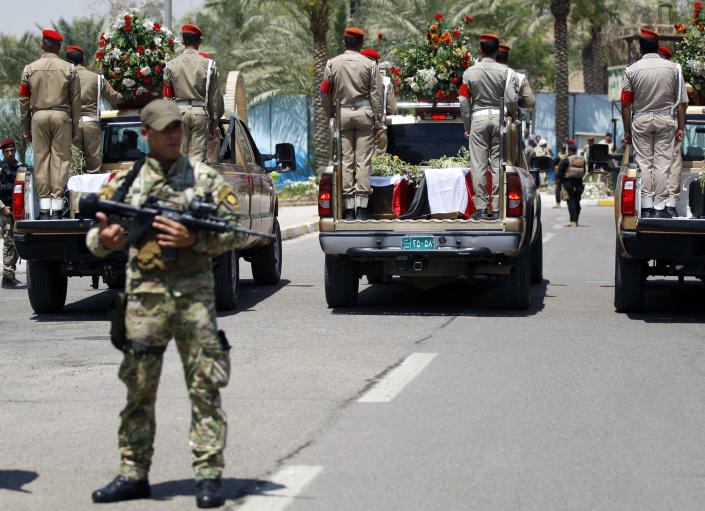 Security forces escort the coffins of five slain soldiers at the headquarters of the Iraqi Ministry of Defense in Baghdad, Iraq, Sunday, April 28, 2012. Gunmen killed 10 people in Iraq, including five soldiers near the main Sunni protest camp west of Baghdad on Saturday, the latest in a wave of violence that has raised fears the country faces a new round of sectarian bloodshed. (AP Photo/Hadi Mizban)