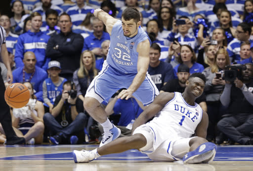 Duke's Zion Williamson (1) falls to the floor with an injury while chasing the ball against North Carolina's Luke Maye (32) during the first half of a college basketball game in Durham, N.C., Wednesday, Feb. 20, 2019. (AP Photo/Gerry Broome)