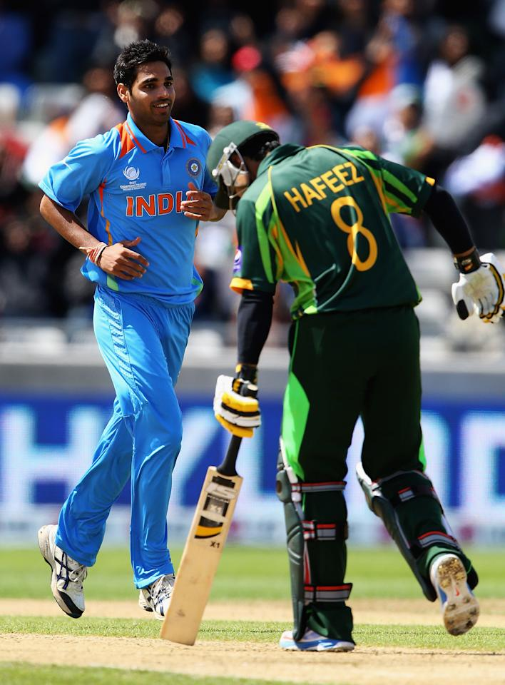 BIRMINGHAM, ENGLAND - JUNE 15:  Bhuvneshwar Kumar of India celebrates the wicket of Mohammad Hafeez  of Pakistan, after he was caught by MS Dhoni during the ICC Champions Trophy Group A match between India and Pakistan at Edgbaston on June 15, 2013 in Birmingham, England.  (Photo by Matthew Lewis-ICC/ICC via Getty Images)