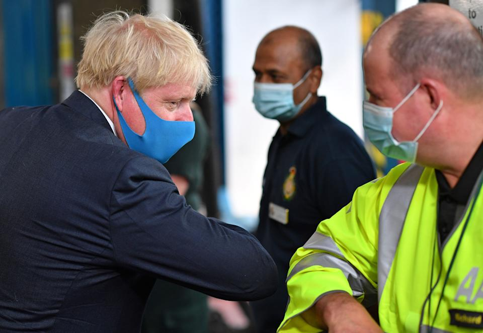 Prime Minister Boris Johnson, wearing a face mask, elbow bumps AA employee Richard during a visit to the headquarters of the London Ambulance Service NHS Trust. (Photo: PA)