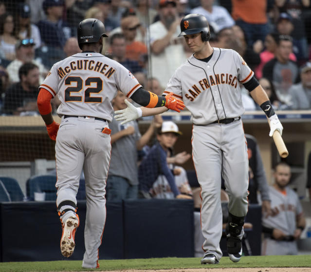 San Francisco Giants' Andrew McCutchen, left, celebrates his solo home run with Buster Posey during the fifth inning of a baseball game against the San Diego Padres in San Diego, Saturday, April, 14, 2018. (AP Photo/Kyusung Gong)