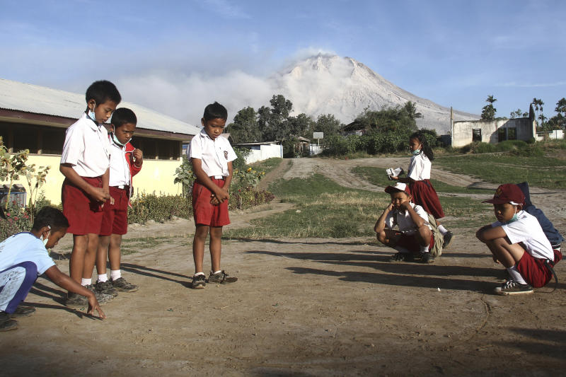 """Students play before the start of their class as Mount Sinabung is seen in the background, at an elementary school in Beganding, North Sumatra, Indonesia, Tuesday, Feb. 20, 2018. Volcanologists say Monday's eruption of the volcano that shot ash 5 kilometers (3 miles) high also """"annihilated"""" the mountain's summit. (AP Photo/Ahmad Putra)"""