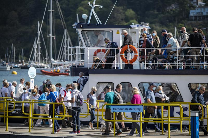 Passengers wearing face coverings to reduce the spread of coronavirus, disembark the Dartmouth Princess ferry from Kingswear to Dartmouth, on the River Dart in Dartmouth, Devon.