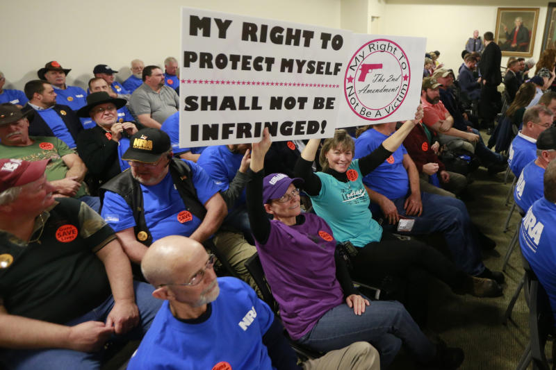 Gun rights protesters hold signs prior to the start of a meeting of the Senate Judiciary committee at the Capitol in Richmond, Va.