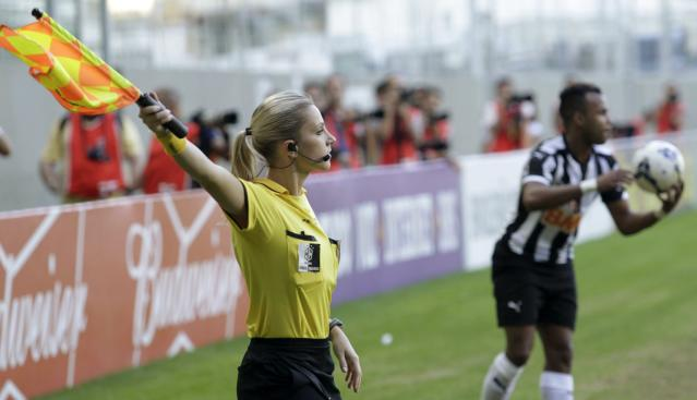 Brazil's referee assistant Fernanda Colombo Uliana signs her flag next to Atletico Mineiro's Fernandinho during the Brazilian championship soccer match between Atletico Mineiro and Cruzeiro in Belo Horizonte May 11, 2014. Uliana has just been granted FIFA official status by the refereeing committee of the Brazilian Football Confederation. REUTERS/Washington Alves (BRAZIL - Tags: SPORT SOCCER)