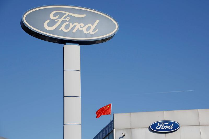FILE PHOTO: Chinese national flag flies on the roof of a Ford car dealership in Beijing