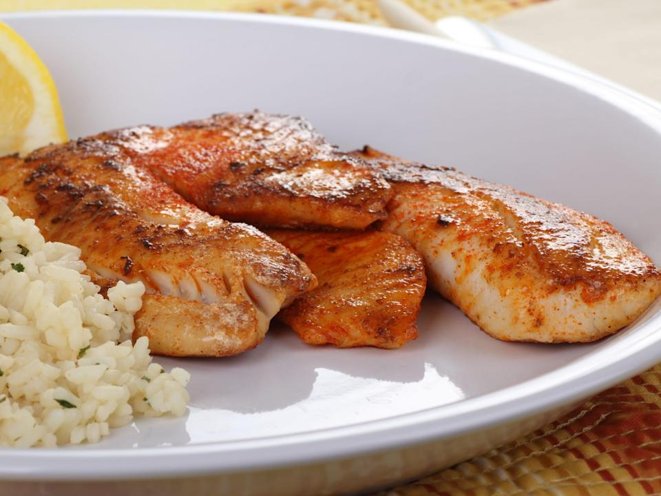Closeup of tilapia fish fillets with rice and a slice of lemon on a plate.