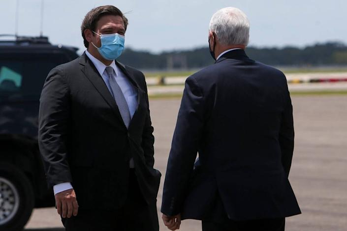 Florida Gov. Ron DeSantis greets Vice President Mike Pence upon his arrival at Tampa International Airport on Thursday, July 2, 2020, in Tampa. The vice president met with the governor regarding the efforts the state is making to combat COVID-19.