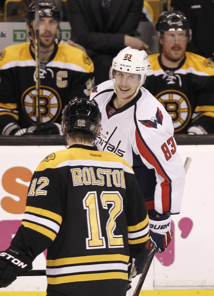 Washington Capitals' Jay Beagle (83) smiles as he skates past the Boston Bruins' Brian Rolston (12) after scoring during the second period of Washington's 4-3 win in Game 5 in a first-round NHL Stanley Cup playoff hockey series in Boston Saturday, April 21, 2012. (AP Photo/Winslow Townson)