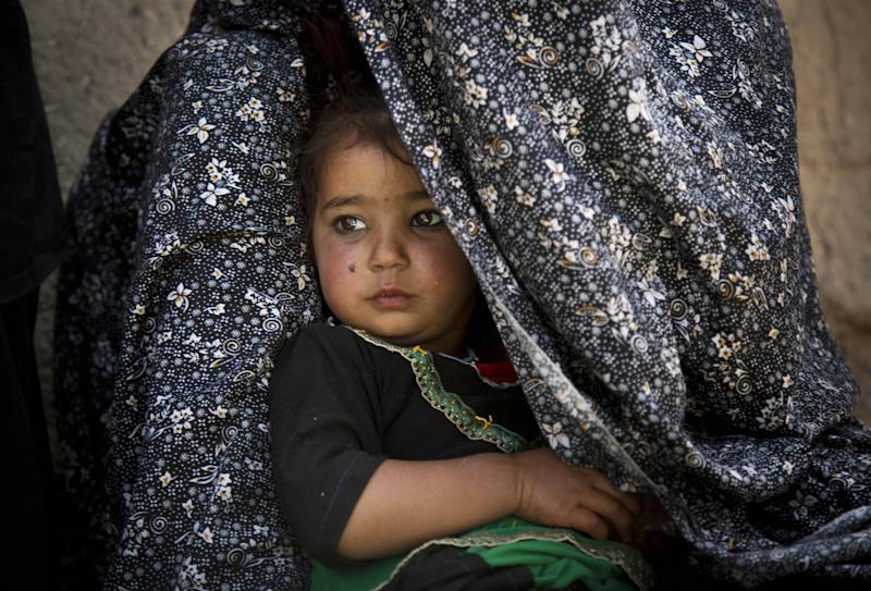 Shahara, now 3, sits tucked inside the shawl of her mother, Masooma, in Kandahar, Afghanistan, on Saturday, April 20, 2013 as Masooma recalls the night she says a U.S. soldier killed her husband and attacked her children in a southern Afghanistan village. Masooma says the soldier grabbed Shahara's pony tails and shook her head violently after killing her father. (AP Photo/Anja Niedringhaus)