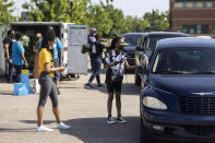 Volunteers Paris Wilkerson, left, and Makhayla DesRosiers, right, distribute Black Voters Matter fans, shirts and wristbands as other volunteers distribute groceries Saturday, May 8, 2021, at Carver High School in Montgomery, Ala. The care packages were part of the program in the John Lewis Advancement Act Day of Action. (AP Photo/Vasha Hunt)