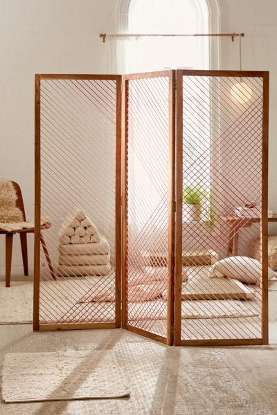 """<h3><a href=""""https://www.urbanoutfitters.com/shop/astra-room-divider-screen"""" rel=""""nofollow noopener"""" target=""""_blank"""" data-ylk=""""slk:Urban Outfitters Astra Room Divider Screen"""" class=""""link rapid-noclick-resp"""">Urban Outfitters Astra Room Divider Screen</a></h3><p>This divider features artful, yarn-screened panels that section off a space without making it feel dark and shut off from the rest.</p><br><br><strong>Urban Outfitters</strong> Astra Room Divider Screen, $299, available at <a href=""""https://www.urbanoutfitters.com/shop/astra-room-divider-screen"""" rel=""""nofollow noopener"""" target=""""_blank"""" data-ylk=""""slk:Urban Outfitters"""" class=""""link rapid-noclick-resp"""">Urban Outfitters</a>"""