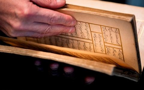 "Dutch art crime investigator Arthur Brand in Amsterdam shows a rare 15th-century book of poems by Shams-ud-din Muhammad Hafiz's ""Divan"". - Credit: KENZO TRIBOUILLARD /AFP"