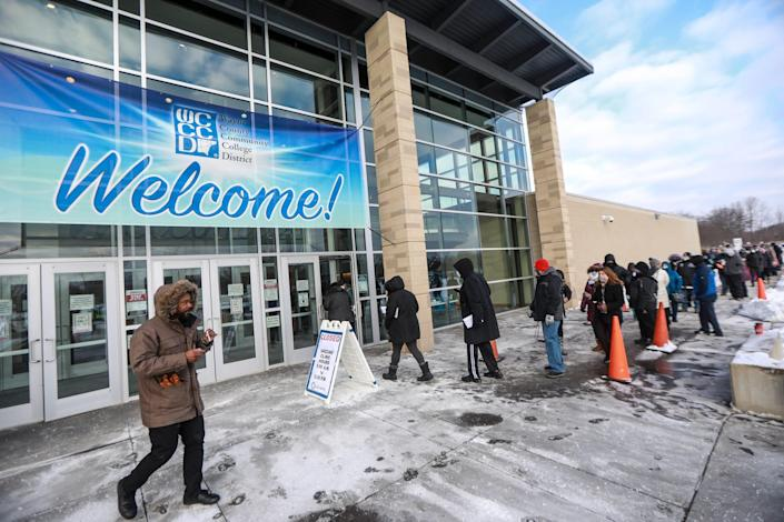 Hundreds of people stand in line outside in 10-degree weather at the Wayne County Community College District Downriver Campus in Taylor for the COVID-19 Pfizer vaccine on Saturday, Feb. 6, 2021.  As many as 2,000 K-12 staff were scheduled to get vaccines that day, as part of the first week of vaccination efforts for educators in the county. The shots were to be given inside the building, but only 300 people could be indoors at once to still maintain social distancing.