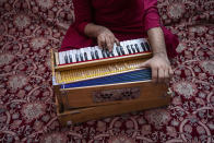 An Afghan musician plays the harmonium during a portrait in Kabul, Afghanistan, Thursday, Sept. 16, 2021. About a month after the Taliban seized power in Afghanistan, the music is starting to go quiet. The last time that the militant group ruled the country, in the late 1990s, it outright banned music. (AP Photo/Bernat Armangue)