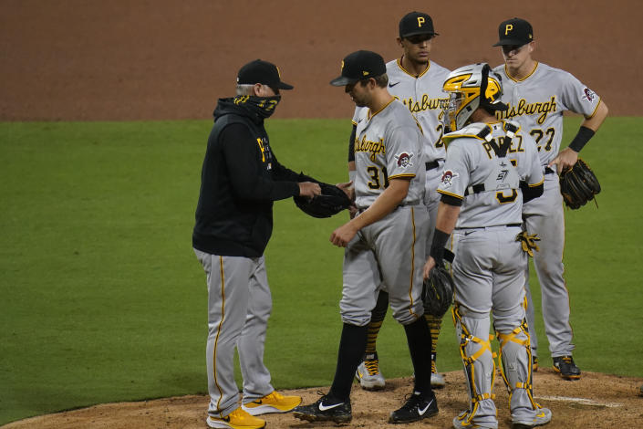 Pittsburgh Pirates manager Derek Shelton, left, takes the ball from starting pitcher Tyler Anderson, second from left, during the seventh inning of a baseball game against the San Diego Padres, Monday, May 3, 2021, in San Diego. (AP Photo/Gregory Bull)