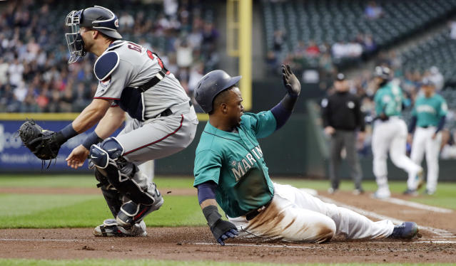 Seattle Mariners' Jean Segura, right, scores as Minnesota Twins catcher Mitch Garver waits for the throw during the first inning of a baseball game Friday, May 25, 2018, in Seattle. (AP Photo/Elaine Thompson)
